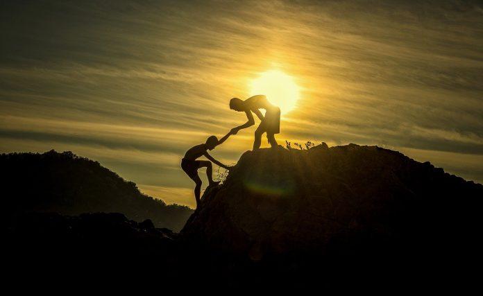 Man helping another man climb a mountain